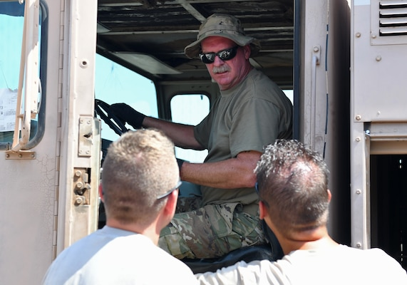 U.S. Air Force Master Sgt. Larry Davidson, top, 776th Expeditionary Air Base Squadron Fuels superintendent, talks to 726th EABS Vehicle Maintenance members during the meter calibration of an R11 refueling truck at Chabelley Airfield, Djibouti, Nov. 8, 2019. The 726th EABS Vehicle Maintenance team service and repair more than 140 Air Force vehicles in the Horn of Africa area of responsibility. (U.S. Air Force photo by Staff Sgt. Alex Fox Echols III)