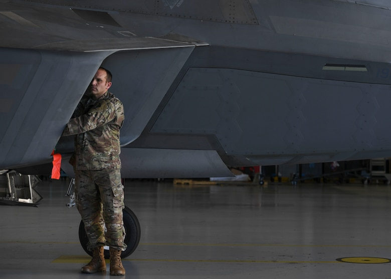 U.S. Air Force Tech. Sgt. Daniel Caban, 1st Aircraft Maintenance Squadron crew chief, covers an F-22 Raptor intake with the Portable Magnetic Aircraft Covers at Joint Base Langley-Eustis, Virginia, Oct. 23, 2019.