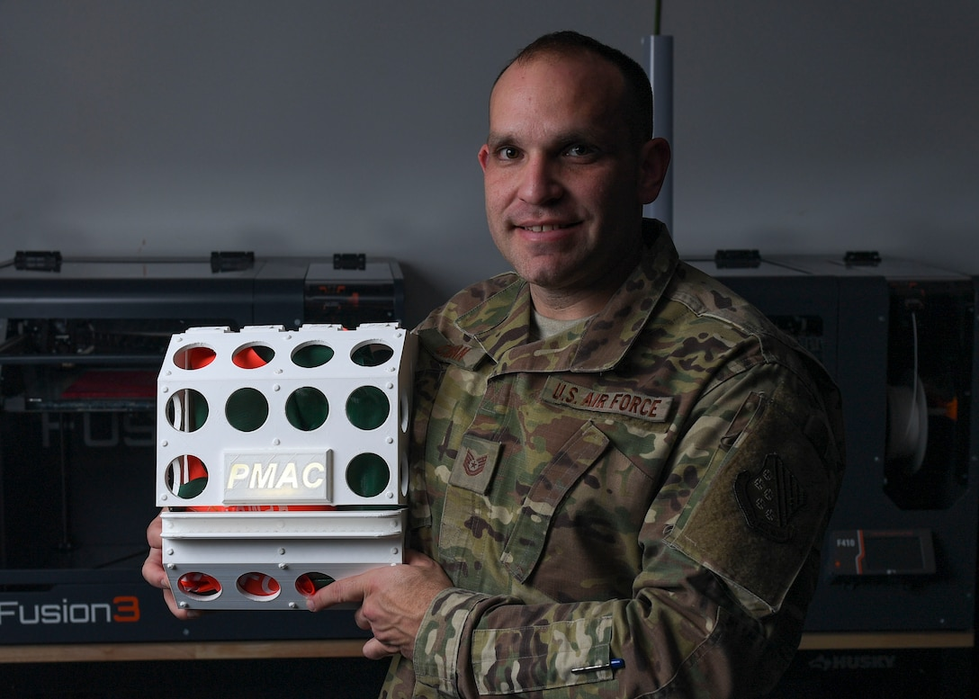 U.S. Air Force Tech. Sgt. Daniel Caban, 1st Aircraft Maintenance Squadron crew chief, poses with his Portable Magnetic Aircraft Covers prototype in the 1st Fighter Wing Innovation Cell Lab at Joint Base Langley-Eustis, Virginia, Nov. 5, 2019.