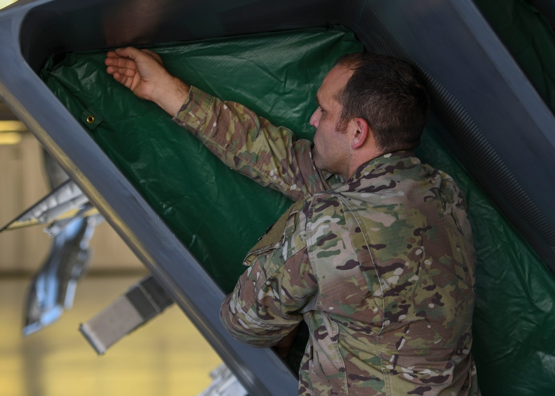 U.S. Air Force Tech. Sgt. Daniel Caban, 1st Aircraft Maintenance Squadron crew chief, applies a portion of the Portable Magnetic Aircraft Covers to an F-22 Raptor intake at Joint Base Langley-Eustis, Virginia, Oct. 23, 2019.