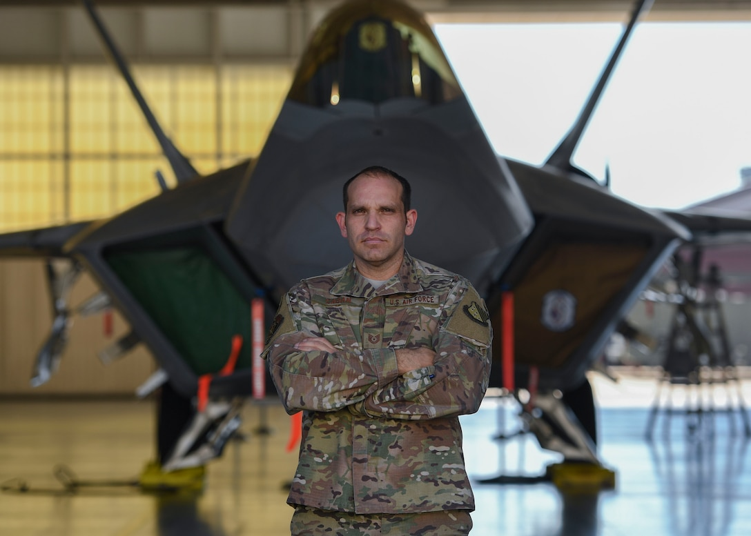 U.S. Air Force Tech. Sgt. Daniel Caban, 1st Aircraft Maintenance Squadron crew chief, stands in front of an F-22 Raptor at Joint Base Langley-Eustis, Virginia, Oct. 23, 2019.
