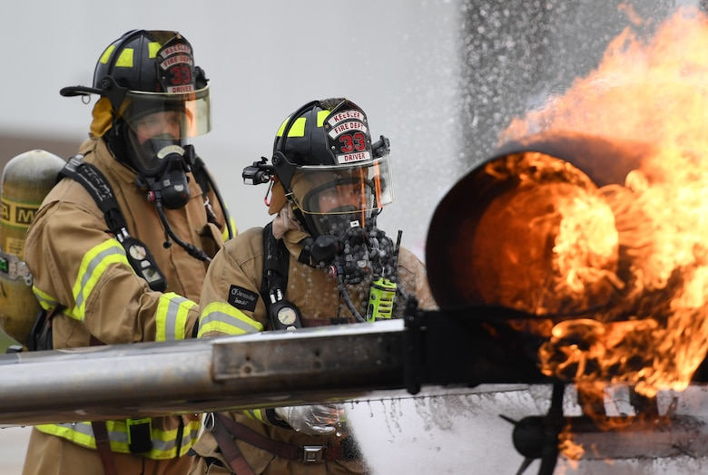 Cole Ballard and Seth Corn, 81st Infrastructure Division firefighters, use a hand-held hose to extinguish a fire on a mock C-123 training device during an aircraft rescue fire fighting training exercise at Keesler Air Force Base, Mississippi, Nov. 8, 2019. The five-day joint agency training allowed the Keesler Fire Department and the Gulfport Combat Readiness Training Center Fire Department to meet the semi-annual training requirement to practice aircraft rescue and live fire training evolutions. (U.S. Air Force photo by Kemberly Groue)