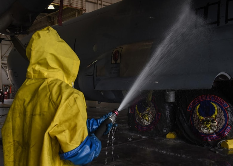 Photo shows an Airman, dressed in yellow protection gear, spraying down cleaning chemicals on the side of a C-130J Super Hercules aircraft.
