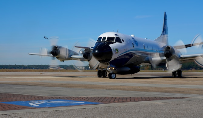 A National Oceanic and Atmospheric Administration Aircraft Operations Center WP-3D Orion aircraft prepares to park on the flightline, as a 53rd Weather Reconnaissance Squadron WC-130J Super Hercules flies in the background at Keesler Air Force Base, Miss., Nov. 13, 2019. Both teams of Hurricane Hunters met to share information and review the 2019 hurricane season. (U.S. Air Force photo by Senior Airman Kristen Pittman)