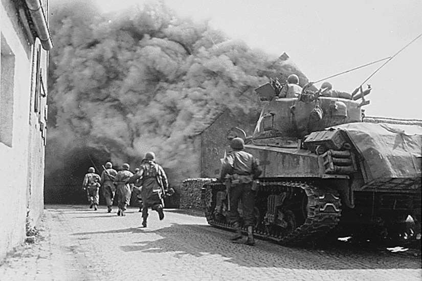 Soldiers run alongside a tank. Smoke billows off a burning home.