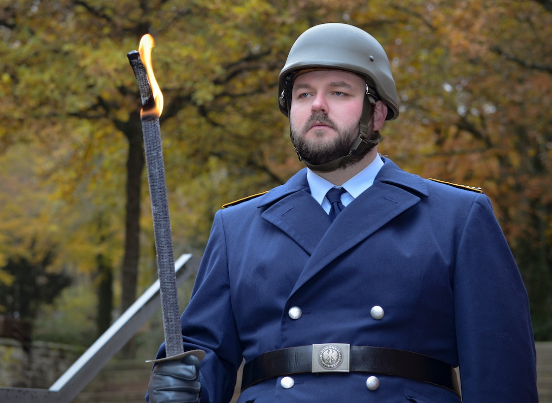 """A German military member holds a ceremonial flaming sword during the City of Kaiserslautern's National Day of Mourning Ceremony, Kaiserslautern, Germany, Nov. 17, 2019. The National Day of Mourning (Volkstrauertag) is an annual German occasion to remember all victims of war and tyranny. It was established in 1922 and was initially dedicated to the victims of World War I. As with the Sunday of the Dead (Totensonntag), the National Day of Mourning is a """"silent day,"""" which means that in some regions of Germany music and dance events are prohibited."""