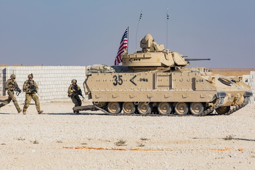 Soldiers run toward a military vehicle on desert terrain.