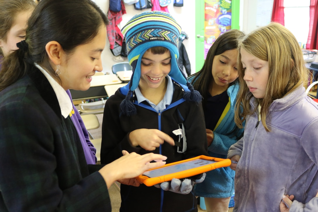 Scientist from Norfolk District holds mobile tablet and explais to smiling children how to work the application