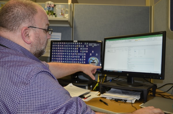 Bryan Mattheis, a systems accountant for business analysis and integration with DLA Finance at DLA Disposition Services, shows a colleague how he uses his spreadsheet system to study inventory data and look for errors that need correction.