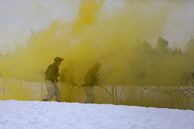 Two soldiers surrounded by yellow smoke  place explosives  in the snow.