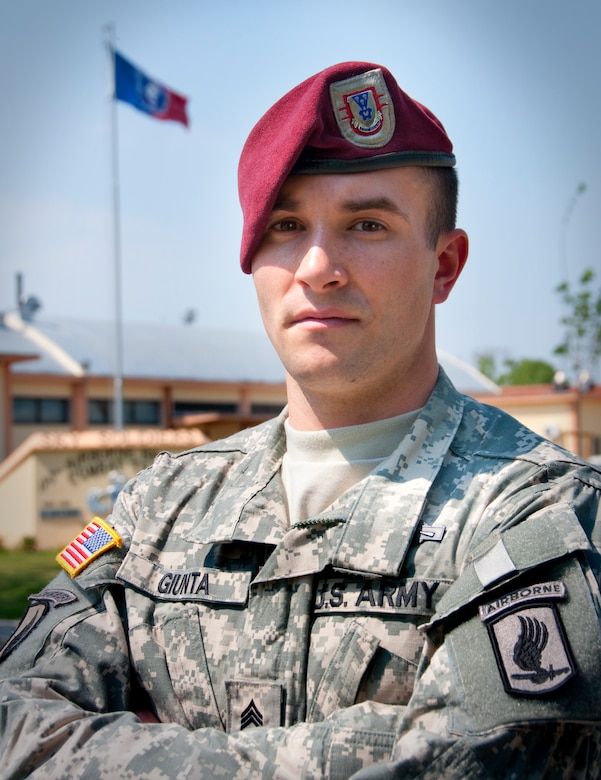 A soldier in uniform and red beret poses with his arms crossed over his chest. A flag flies in the background.