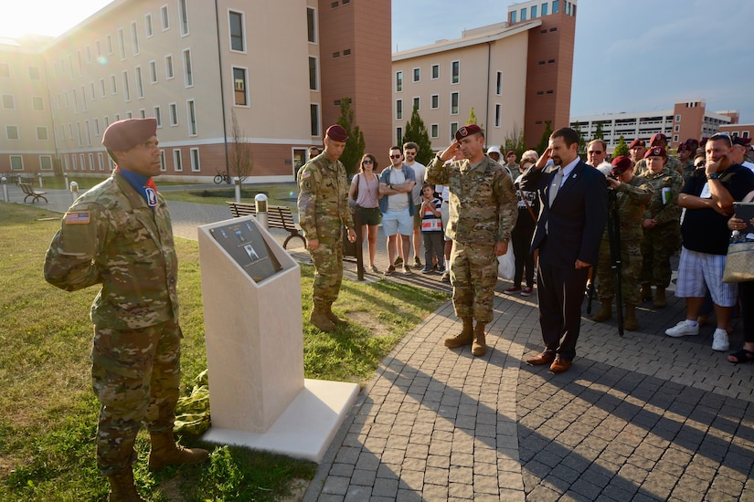 An Army commander and a veteran in plain clothes salute a memorial plaque on a walkway. Other soldiers stand at attention around it. Civilians also look on.