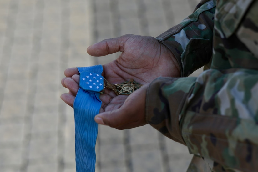 The Medal of Honor is held in the hands of a soldier in long-sleeve uniform.