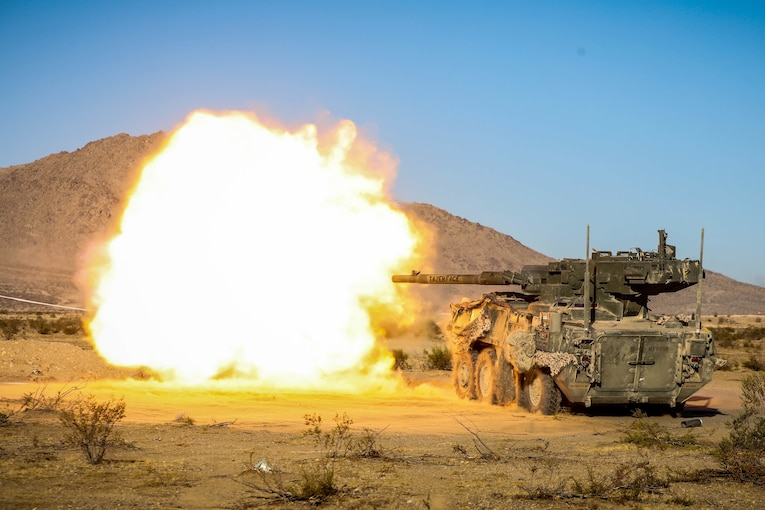 An Army howitzer shoots, creating a massive fireball.