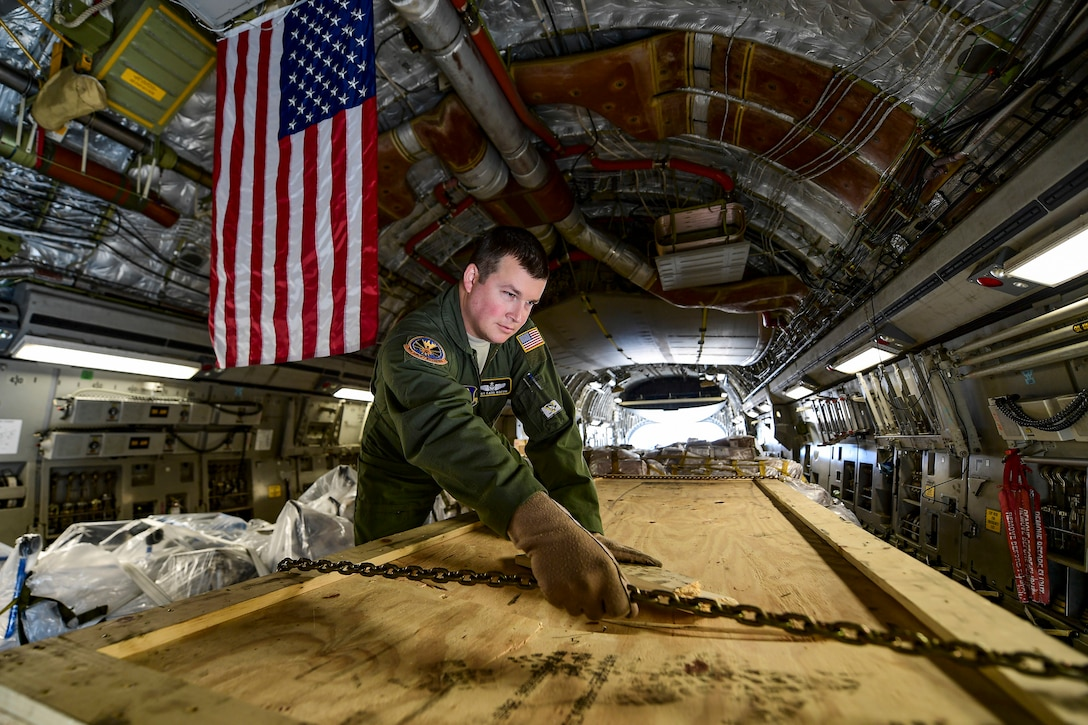 An airman handles a chain over a wooden container inside an aircraft.