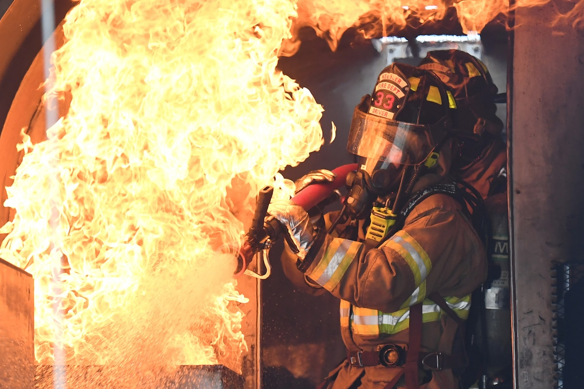 Two airmen in firefighting uniforms spray water on flames.
