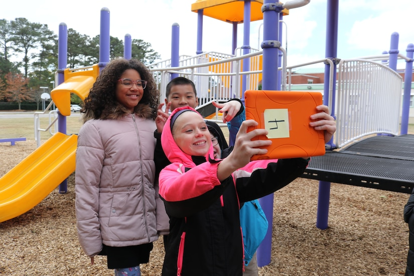 One child holds up mobile tablet to take a selfie, while four friends smile in background