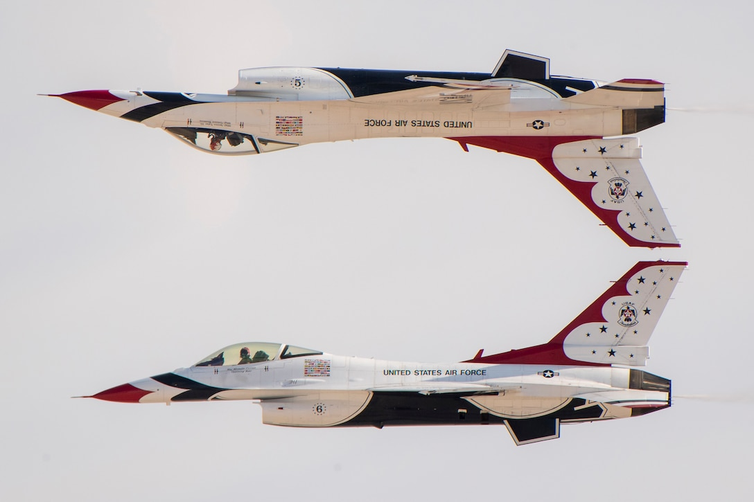 A military jet flies upside down above another military jet.