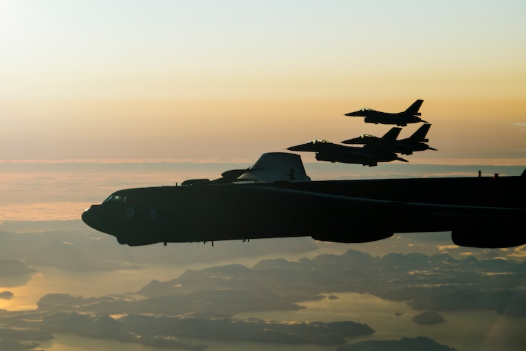 Four military aircraft fly side by side at twilight.
