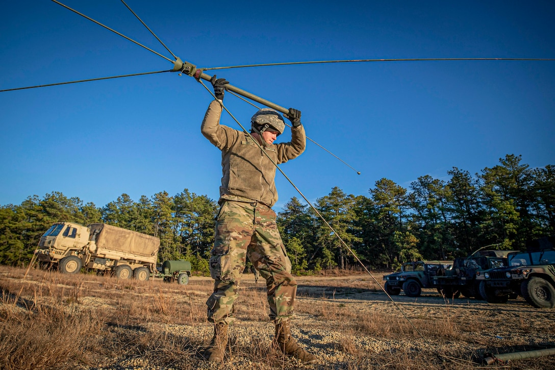 A soldier holds an antenna-like object over his head in a field.