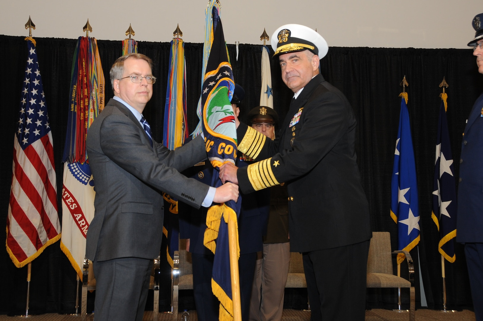 U.S. Navy Adm. Charles A. Richard accepts the U.S. Strategic Command guidon from Deputy Secretary of Defense David L. Norquist as he assumes command of U.S. Strategic Command (USSTRATCOM) during a change of command ceremony at Offutt Air Force Base, Neb., Nov. 18, 2019. Richard comes to USSTRATCOM after serving as the commander of Submarine Forces; commander of Submarine Force Atlantic and commander of Allied Submarine Command at Naval Station Norfolk, Va. USSTRATCOM has global responsibilities assigned through the Unified Command Plan that include strategic deterrence, nuclear operations, joint electromagnetic spectrum operations, global strike, missile defense, and analysis and targeting. (U.S. Air Force photo by Steve Cunningham)