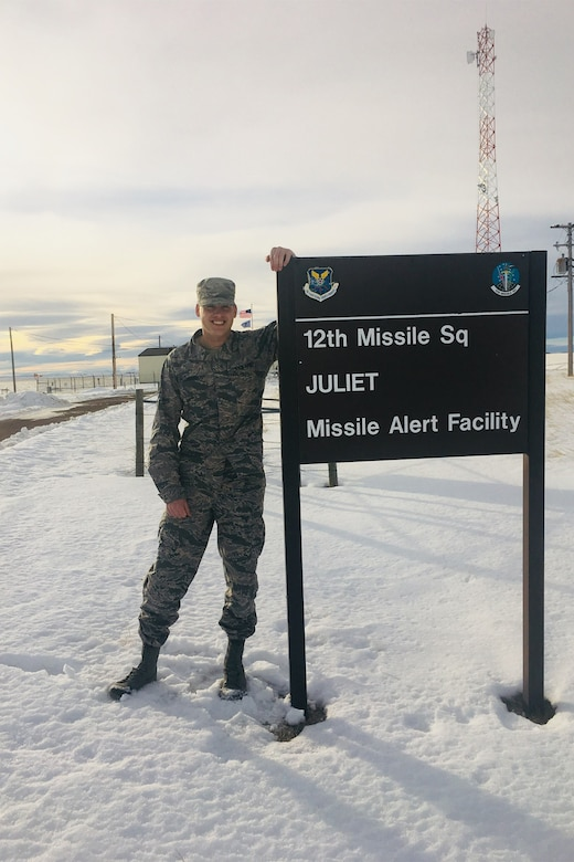 Then Staff Sgt. Clay Barnard, formerly a 12th Missile Squadron missile alert facility manager, poses for a picture by a sign at Juliet missile alert facility near Malmstrom Air Force Base, Mont.