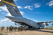 U.S. service members with Marine Light Attack Helicopter Squadron 369, 3rd Marine Aircraft Wing (MAW) unload a U.S. Marine Corps AH-1Z Cobra from a U.S. Air Force C-17 Globemaster III at Marine Corps Air Station Futenma in Okinawa, Japan, Nov. 11, 2019. The C-17 delivered the cobra as part of a MAW semi-annual aircraft swap within the unit deployment program. (U.S. Marine Corps photo by Cpl. Savannah Mesimer)