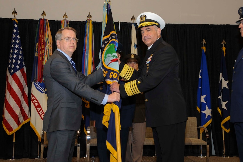 Deputy Defense Secretary David L. Norquist and Navy Adm. Charles A. Richard hold onto a flag together.