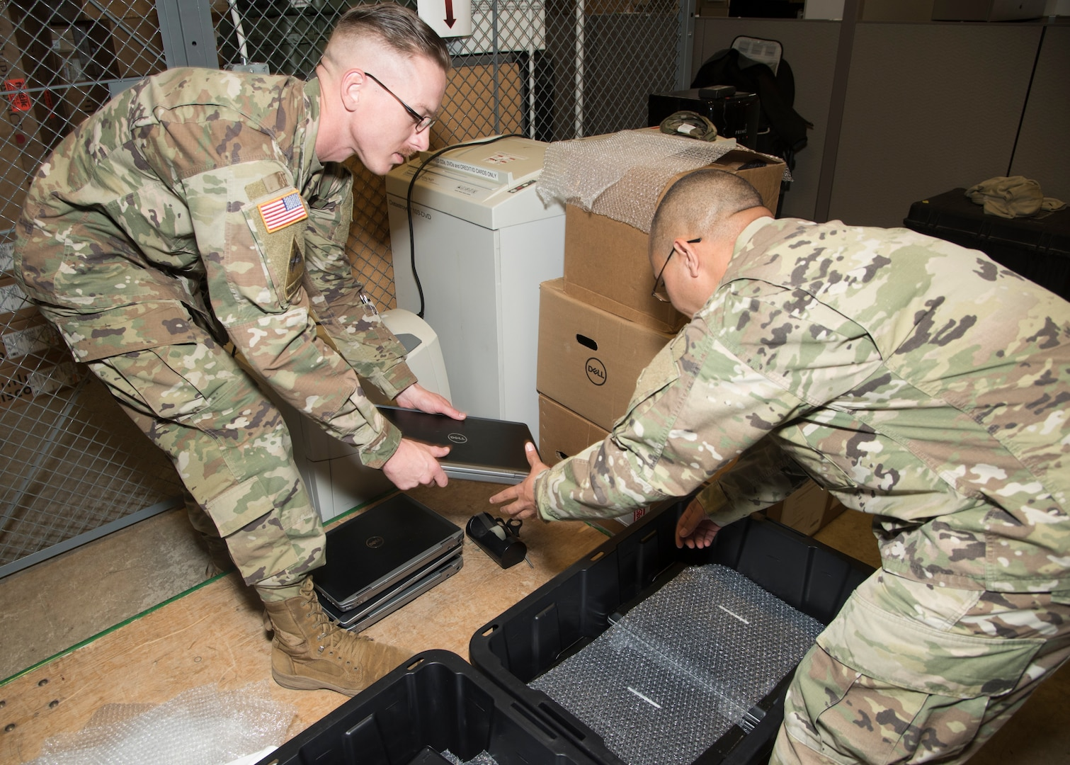 Army Staff Sgt. Marvin Tyler Nelson and Sgt. 1st Class Eugenio Moya, U.S. Army North, pack computers for transport to Wilkinson County High School in Woodville, Mississippi. The computers are being donated to the school through the Department of Defense's Computers for Learning program.