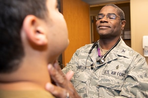 Photo of Col. Dennis Britten performing routine health assessment on patient.