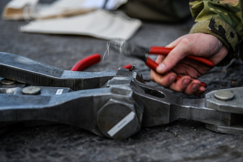 U.S. Airmen from the 31st Maintenance Squadron place a pin into a lifting sling at Aviano Air Base, Italy, Nov. 16, 2019. The 31st Maintenance Squadron provides accessory maintenance, avionics, periodic phase inspections, fabrication, and aerospace ground equipment for 50 assigned aircraft. (U.S. Air Force photo by Airman 1st Class Ericka A. Woolever).