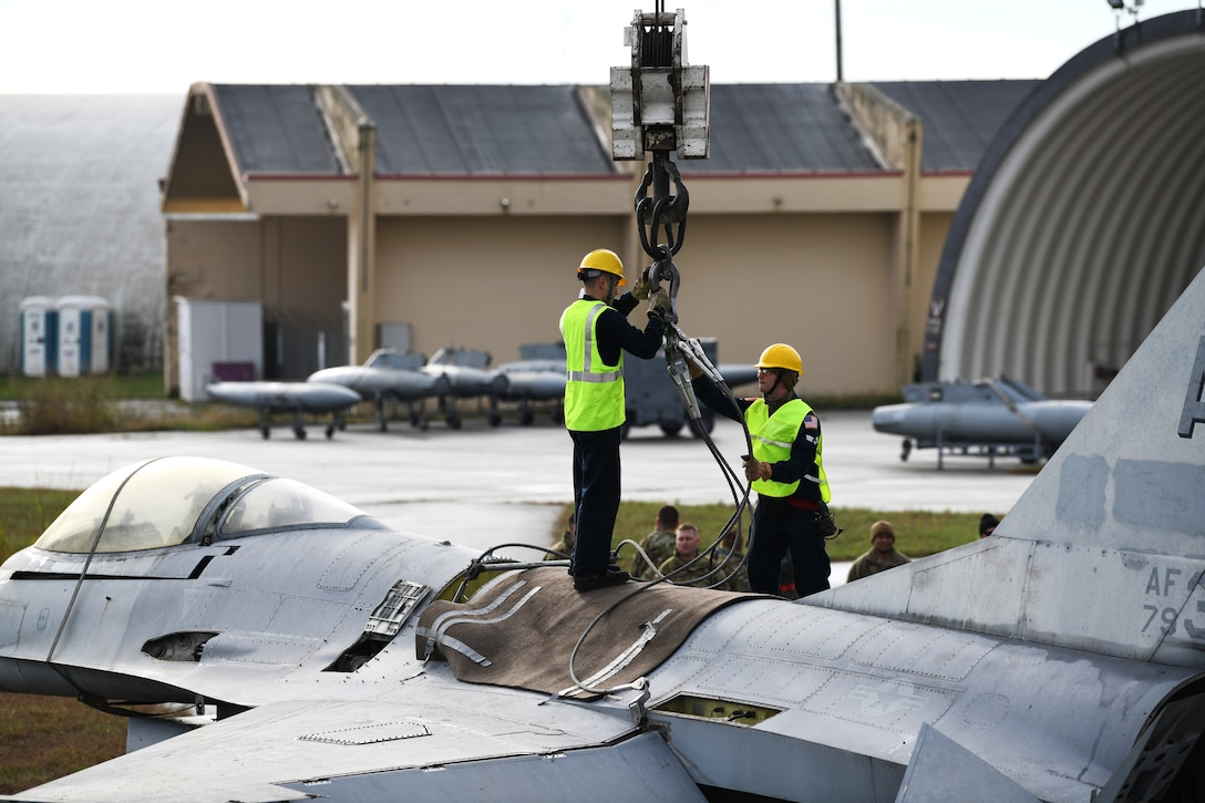 U.S. Airmen from the 31st Maintenance Squadron unhook a F-16 Fighting Falcon from the lifting sling attached to a 60 ton crane at Aviano Air Base, Italy, Nov. 16, 2019. The lifting sling and guide ropes were used to keep the F-16 stable during the lift. (U.S. Air Force photo by Airman 1st Class Ericka A. Woolever).