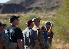 Adrianne Rankin (second from right), 56th Range Management Office archaeologist, briefs Luke Air Force Base commanders and honorary commanders on Native American petroglyphs Nov. 14, 2019, at the Chris Glyphs Archeological Site, Ariz.