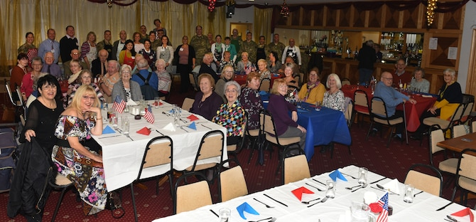 Volunteers from Team Mildenhall and its British-American Committee pose for a photo with senior citizens in the local community at the Mildenhall Social Club, Mildenhall, England, Nov. 18, 2019. Base leadership, Airmen and BAC members served the luncheon to build relations and give back to the local community. (U.S. Air Force photo by Karen Abeyasekere)