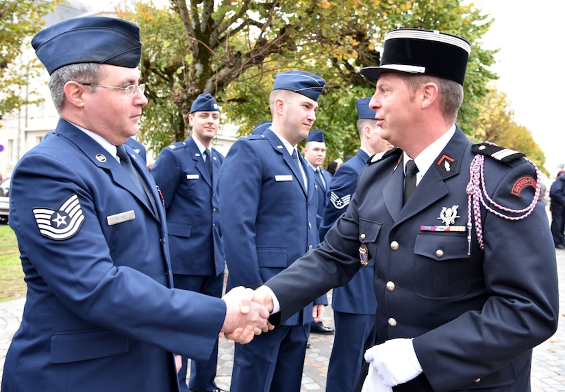 U.S. Air Force Tech. Sgt. Jeremy Becnel, 305th Operations Support Squadron boom instructor, greets a French Fire Services officer prior to taking part in an Armistice Day commemoration Nov. 11, 2019, in Issoudun, France. The Airmen helped commemorate the day and honor fallen Airmen who were stationed at the 3rd Aviation Instruction Center during World War I. (U.S. Air Force photo by Tech. Sgt. Chris Powell)