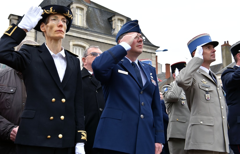 U.S. Air Force Maj. John Cockburn (center), 32nd Aerial Refueling Squadron operations officer, salutes during the French national anthem, along with members of the French government, during an Armistice Day commemoration Nov. 11, 2019, in Issoudun, France.  Airmen from the 32nd ARS at Joint Base McGuire-Dix-Lakehurst, New Jersey, attended the ceremony to help commemorate the day and honor fallen Airmen who were stationed at the 3rd Aviation Instruction Center during World War I. (U.S. Air Force photo by Tech. Sgt. Chris Powell)