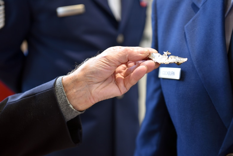 A French military veteran holds an aviation badge given to him by U.S. Air Force Maj. John Cockburn, 32nd Aerial Refueling Squadron operations officer, after an Armistice Day commemoration Nov. 11, 2019, in Issoudun, France. Airmen from the 32nd ARS at Joint Base McGuire-Dix-Lakehurst, New Jersey, attended the ceremony to help commemorate the day and honor fallen Airmen who were stationed at the 3rd Aviation Instruction Center during World War I. (U.S. Air Force photo by Tech. Sgt. Chris Powell)