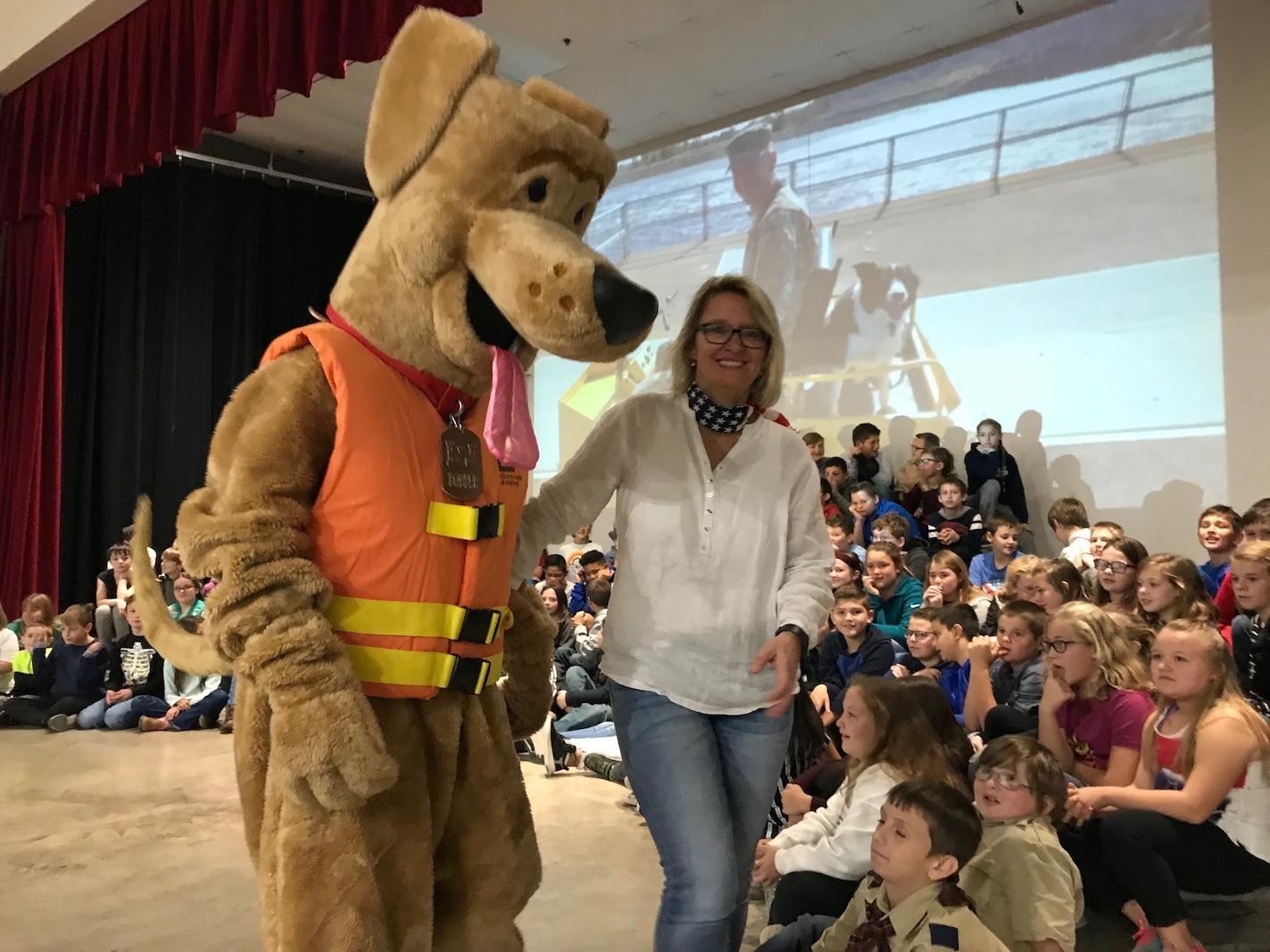 Cleveland, Okla., Intermediate School music and art teacher, Anja Johnson, introduces Bobber, the U.S. Army water safety dog, to school children as part of their annual Veterans Day recognition ceremony. Bobber helped pay tribute to veterans in the audience and also provided each child in attendance a grab-bag of water safety supplies and informational brochures.