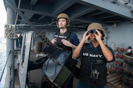 Master-At-Arms Seaman Khang Ho, right, and Seaman Shane Mitchell search for surface contacts during a Strait of Hormuz transit aboard the guided-missile cruiser USS Leyte Gulf (CG 55). Leyte Gulf is deployed to the U.S. 5th Fleet area of operations in support of naval operations to ensure maritime stability and security in the Central Region, connecting the Mediterranean and Pacific through the Western Indian Ocean and three strategic choke points.
