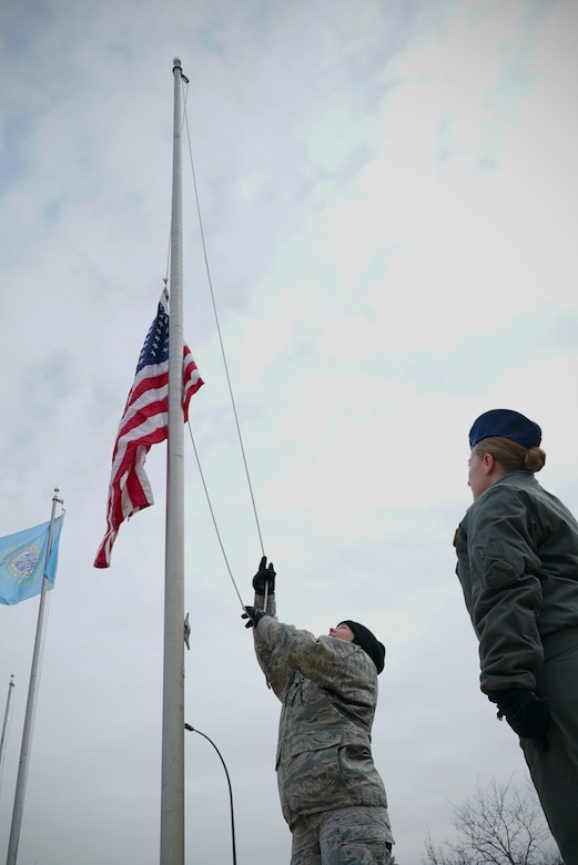 Second Lt. Maria Castle, 348th Reconnaissance Squadron chief of intelligence training, raises a United States flag Nov. 8, 2019, on Grand Forks Air Force Base, North Dakota. Members of the 348 RS volunteered to replace the base's avenue of state flags with that of the U.S. flag, doing so for Veterans Day to honor all who have served in the U.S. military past and present. (U.S. Air Force photo by Senior Airman Elora J. Martinez)