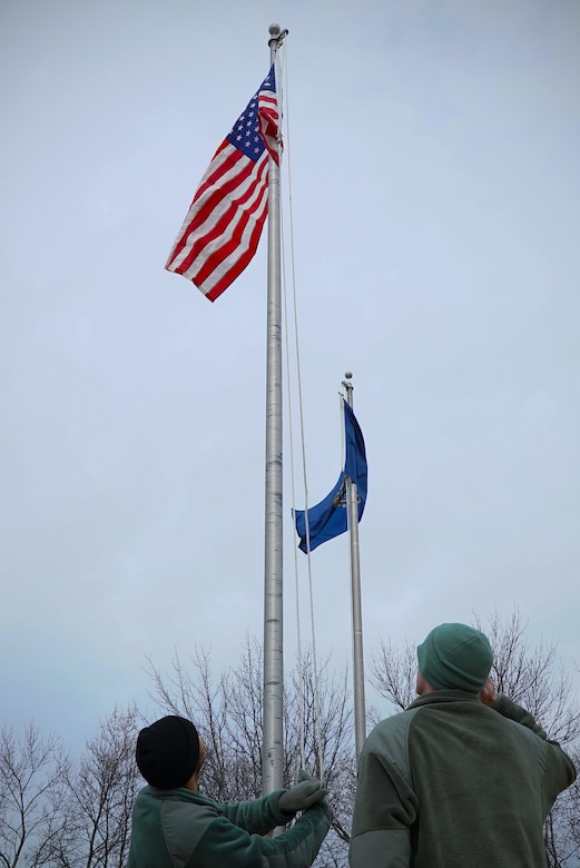 Airmen with the 348th Reconnaissance Squadron raise and salute a United States flag Nov. 8, 2019, on Grand Forks Air Force Base, North Dakota. All state flags at the installation entrance were lowered and switched to U.S. flags by the 348 RS for Veterans Day. (U.S. Air Force photo by Senior Airman Elora J. Martinez)