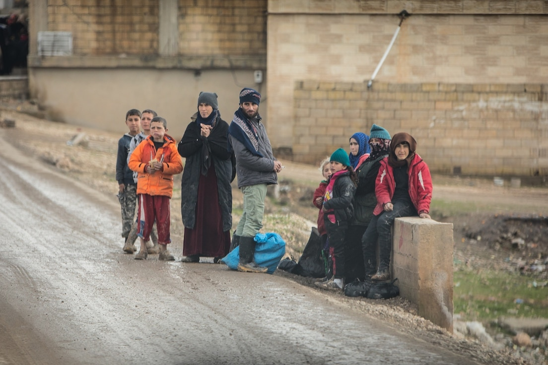 A group of children and parents await a bus to get to school in Ayn Issa, Syria, Dec. 31, 2018. Coalition Forces continue to train, assist, and advise partner forces to maintain regional stability. (U.S. Army Photo by Staff Sgt. Ray Boyington)