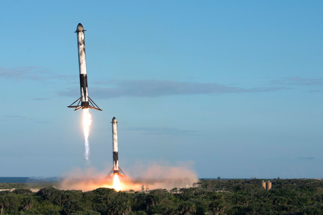 Two rocket boosters descend from the sky.