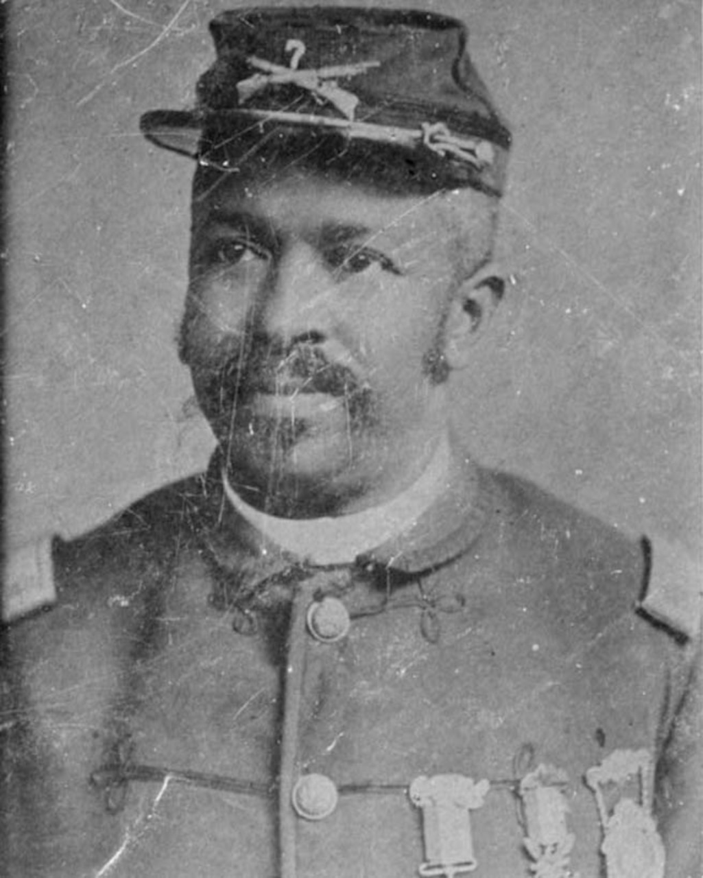 A black Civil War soldier wears his cap and uniform with three medals pinned to his dress shirt.