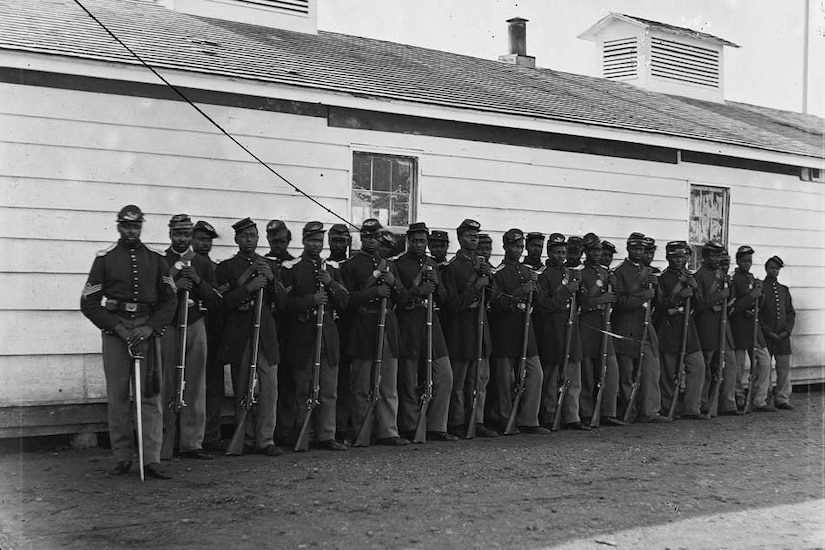 More than two-dozen black Civil War soldiers stand in two lines with their rifles resting on the ground in front of a white building.