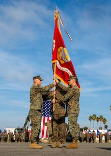 U.S. Marine Corps Col. Jay M. Holtermann, right, the 15th Marine Expeditionary Unit outgoing commanding officer, passes the colors to Col. Christopher J. Bronzi, incoming commanding officer, during a change of command ceremony at Marine Corps Base Camp Pendleton, California, Nov. 13, 2019.