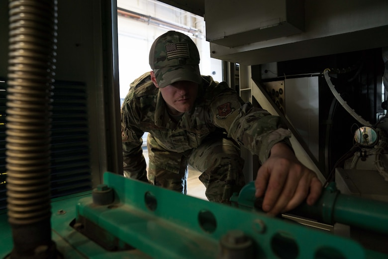 Senior Airman Justin Harrison, 90th Missile Maintenance Squadron, Facility Maintenance Section, support section supervisor, shows how the bump cap can prevent head injuries while performing maintenance on a portable air condition unit on F.E. Warren AFB, Wyoming, Nov. 18, 2019. Tech. Sgt. Haisen Exon, 90 MMXS/FMS, support section NCOIC, teams up with the 90th Missile Wing LaunchWerx agency to bring forward an idea to prevent future head injuries across the wing. (U.S. Air Force photo by Joseph Coslett)
