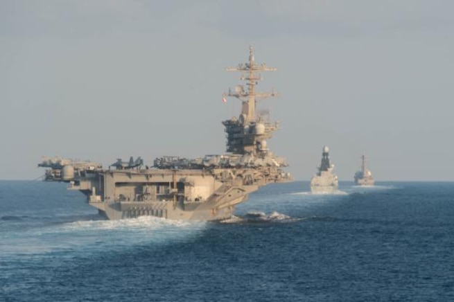 STRAIT OF HORMUZ (Nov. 19, 2019) The aircraft carrier USS Abraham Lincoln (CVN 72), left, the air-defense destroyer HMS Defender (D 36) and the guided-missile destroyer USS Farragut (DDG 99) transit the Strait of Hormuz with the guided-missile cruiser USS Leyte Gulf (CG 55). Leyte Gulf is deployed to the U.S. 5th Fleet area of operations in support of naval operations to ensure maritime stability and security in the Central Region, connecting the Mediterranean and Pacific through the Western Indian Ocean and three strategic choke points. (U.S. Navy photo by Mass Communication Specialist 3rd Class Zachary Pearson/Released)