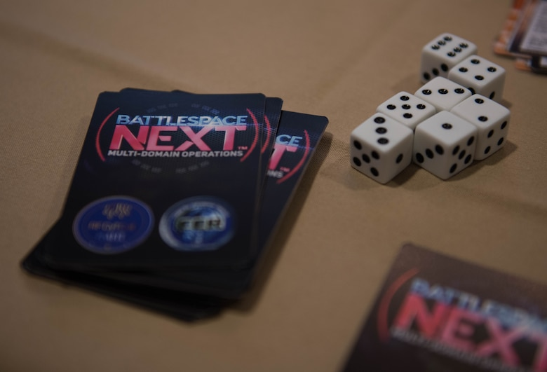 A deck of Battlespace Next cards and dice sit on a table at Joint Base Langley-Eustis, Virginia, Nov. 18, 2019. U.S. Air Force Capt. Nathaniel Flack, Department of Electrical and computer engineering student at the Air Force Institute of Technology, created the game for Airmen to become familiar with modern day issues in a different type of learning environment. (U.S. Air Force photo by Airman 1st Class Sarah Dowe)