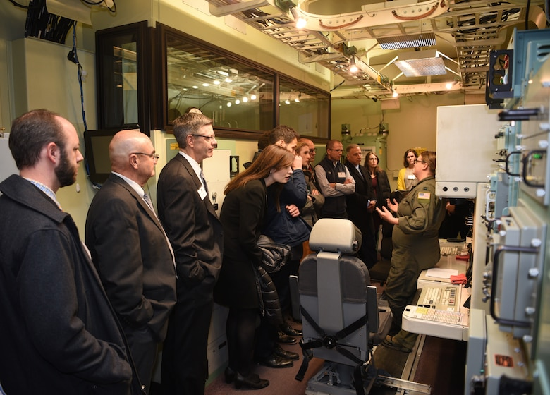Capt. Amanda Schuyler from the 90th Operations Support Squadron, explains the Missile Procedures Trainers to a visiting group from the local chapter of the American Inns of Court during a tour on base Nov. 7, 2019, on F. E. Warren Air Force Base, Wyo. Members of the Inns of Court included justices from the state supreme court, law professors from the University of Wyoming, and local attorneys. The tour was intended to promote stronger relationships between the base legal professionals and their local civilian counterparts. (U.S. Air Force photo by Glenn S. Robertson).